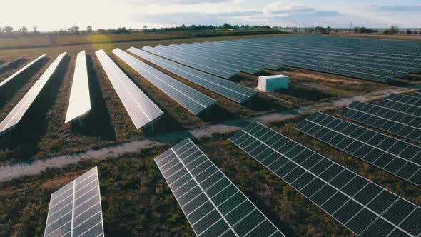 Thumbnail for Aerial Shot of a Solar Power Station with a Way in It at Sparkling Sunset