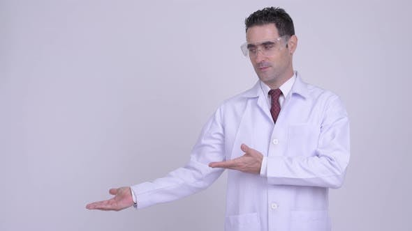 Thumbnail for Happy Handsome Man Doctor with Protective Glasses Showing Something
