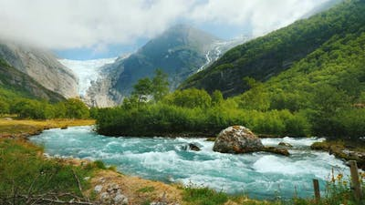 Wide Lens Shot: Briksdal Glacier with a Mountain River in the Foreground. The Amazing Nature of