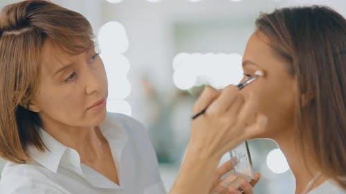 Makeup Artist Completes Makeup, Woman Thanks Makeup Artist. Beauty Studio. Portrait View.