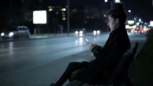 Girl Waiting For Her Friend On The Bench, Texting a Friend From Smartphone