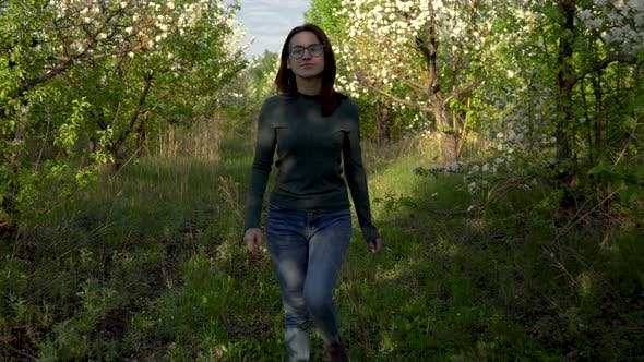 Thumbnail for A Young Woman Walks Between Apple Trees. A Girl Walks Through a Flowering Garden. Front View.