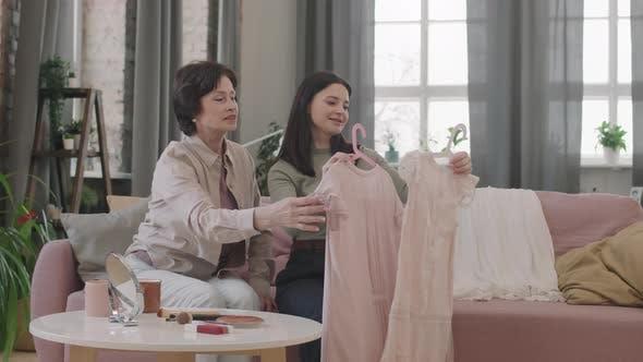 Women Choosing Outfit For Little Girl