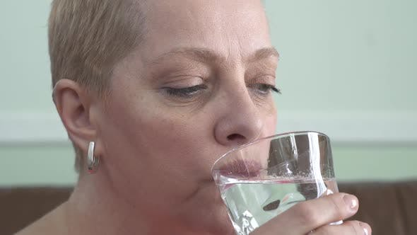 Thumbnail for Portrait of Mature Woman with Short Blond Hair Who Drinking Water From the Glass