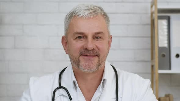 Portrait Of Male Doctor Smiling Sitting In Clinic Office