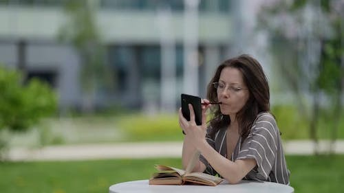 Business Lady Student Studying Science in City Park with Phone and Book