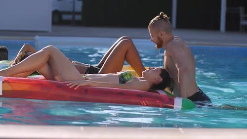 Playful Diverse Friends Relaxing in Swimming Pool