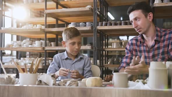 Thumbnail for Cute Caucasian Boy with His Father Making Ceramic Pots in the Pottery