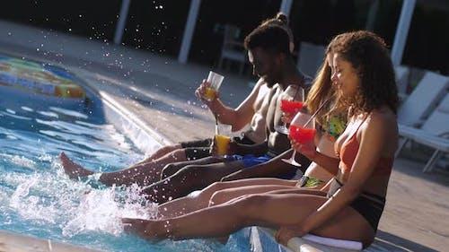 Joyful Friends Kicking Water Splashing in Pool