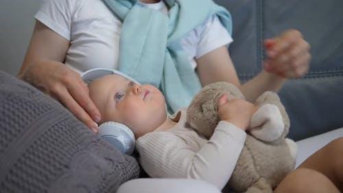 Progressive Mom Puts Earphones on Little Girl to Listen to Audio Book with Fairy Tales
