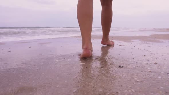 Girl Walks on the Beach on the Background of the Sea