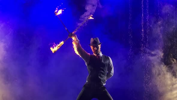 Thumbnail for An Enchanting Show of Fire in Rain and Water Drops Performed By a Stylish Man. Smoky Studio