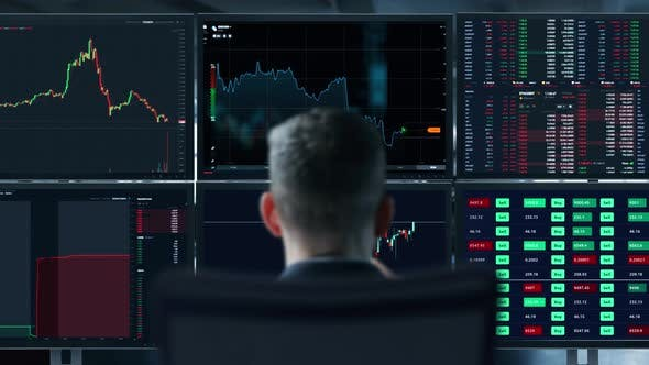 Trader is Working with Multiple Computer Screens Full of Charts and Data Analysis and Stock Broker