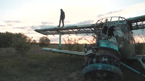 Man Walks on Wing of Maize Airplane with a Disassembled Fuselage, Located in Field with Thick Grass