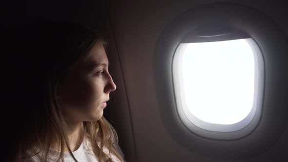 Thumbnail for Girl Sitting By Aircraft Window and Looking Outside