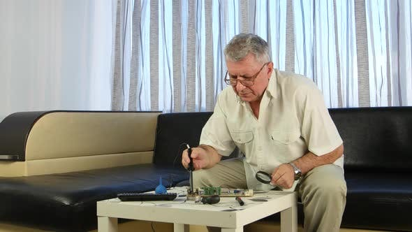 Thumbnail for Älterer Mann Löten ein Brett mit einem Lötkolben, Er hat in seinen Händen eine große Lupe