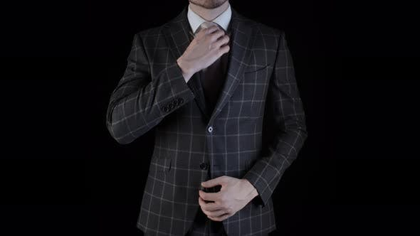 Thumbnail for Handsome Businessman Wearing Suit Straightens His Necktie with Hand Isolated on Black Background
