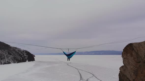 Thumbnail for Man Sitting in a Hammock Mounted at High Altitude Over a Frozen Lake