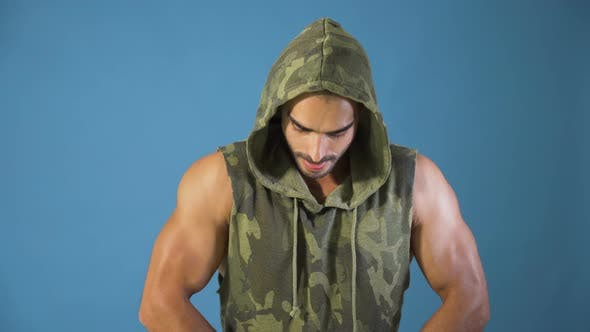 Thumbnail for Bodybuilder in Camouflage Hoodie Flexing Biceps Muscles and Chests, Studio Shot