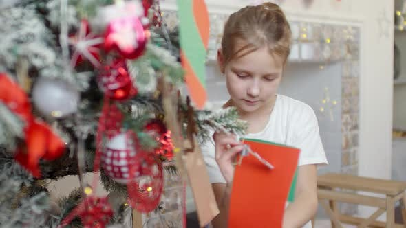 Thumbnail for Little Girl Putting Decorations on Christmas Tree at Home