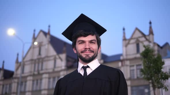 Thumbnail for Attractive Smiling Male Graduate Standing and Looking at Camera.