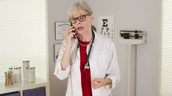 Cover Image for Mature woman doctor smartphone talking