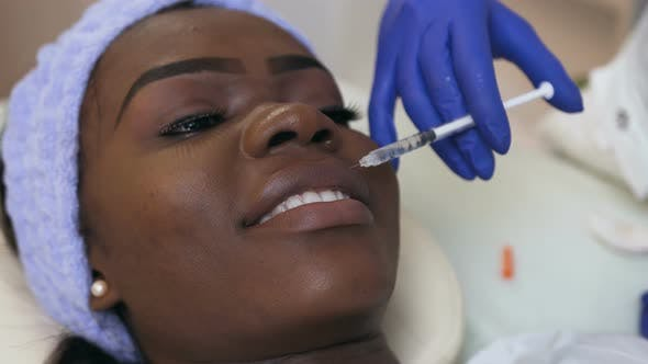 Cosmetologist Hands Making Beauty Injection for Young African Woman