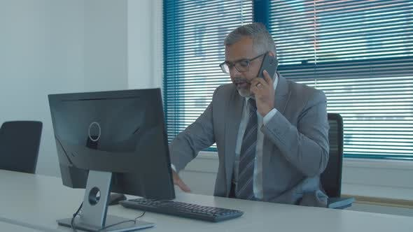 Thumbnail for Focused Grey Haired Business Leader Talking on Mobile Phone