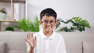 Boy smiling and waving hand.