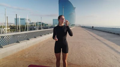 Cheerful Sportswoman Drinking Water During Break