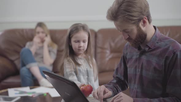 Thumbnail for Portrait of the Bearded Man Working with Tablet Close Up. Little Girl Unsuccessfully Trying To Give
