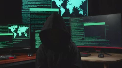 Hacker No Face Pose With Code On Multiple Computer Screens In Dark Room