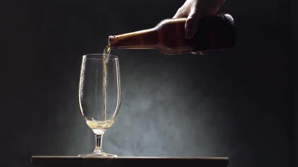 Bier, das in ein Glas vor schwarzem Hintergrund gießt