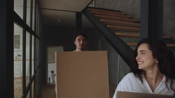 Thumbnail for Smiling Man and Woman Putting Paper Boxes on Floor in Slow Motion.