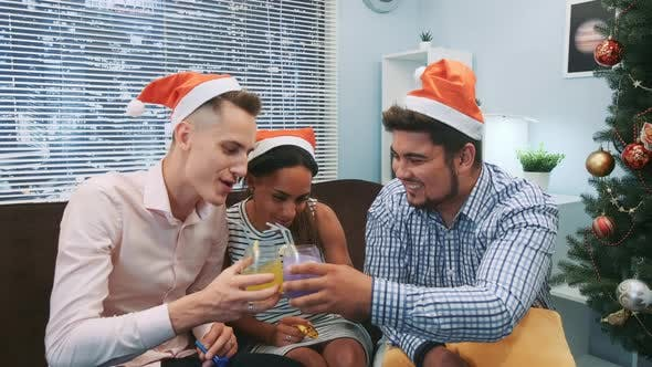 Close Up of Two Boys and a Girl in Santa Hats Making Cheers and Blowing Party Whistles