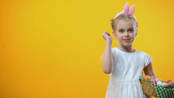 Thumbnail for Happy Easter Text, Cute Child With Eggs Basket in Bunny Ears Showing Thumbs Up