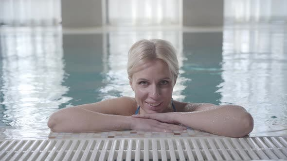 Thumbnail for Blond Smiling Woman Posing at Poolside. Portrait of Happy Young Caucasian Lady Resting in Spa in