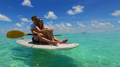 Happy man and woman on honeymoon vacation spend quality time on beach on sunny white sandy