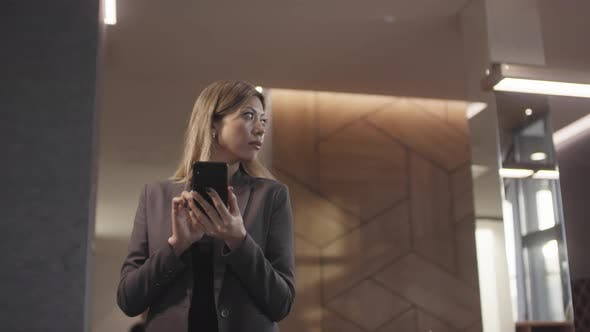 Thumbnail for Businesswoman in Mobile Phone in Hotel Lobby