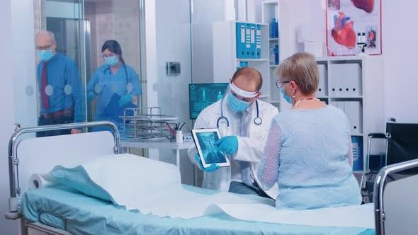 Arzt in Schutzvisier im Gespräch mit Patienten