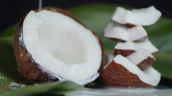 Thumbnail for Coconut Milk Flows To the Pieces of Coconut with Leaves.