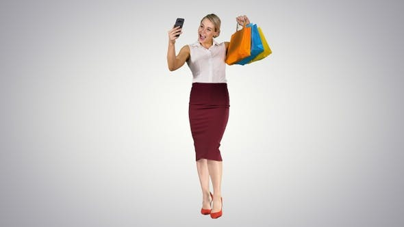 Thumbnail for РЎheerful woman with shopping bags taking selfie on gradient