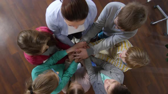 Thumbnail for Six Teenagers and Teacher Joining Hands
