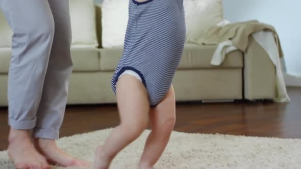 Thumbnail for Toddler Taking First Steps with Support