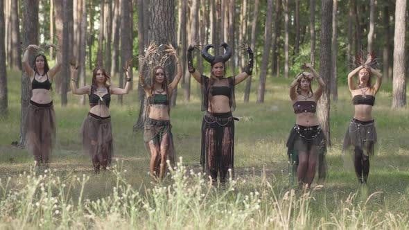 Cover Image for Young Women in Theatrical Costumes of Forest Dwellers or Devils Dancing Arabic Dance in Forest