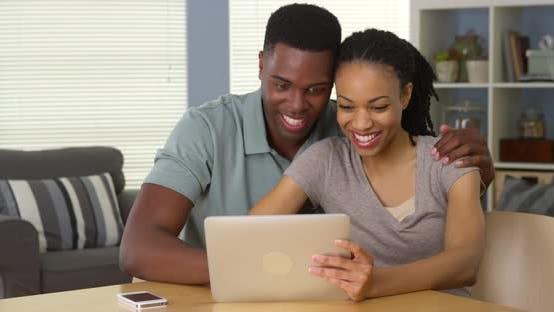 Thumbnail for Happy young black couple using tablet computer together laughing