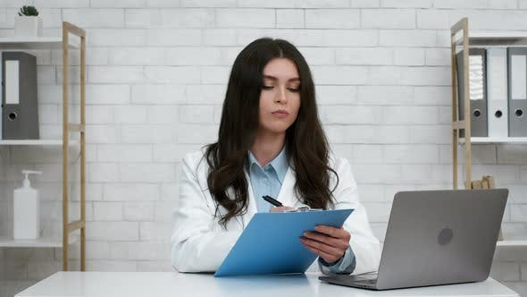 Female Doctor Taking Notes And Nodding Head Sitting In Office
