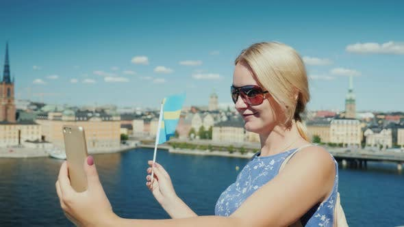 Thumbnail for A Happy Tourist with the Flag of Sweden Takes Pictures of Himself Against the Backdrop of Stockholm