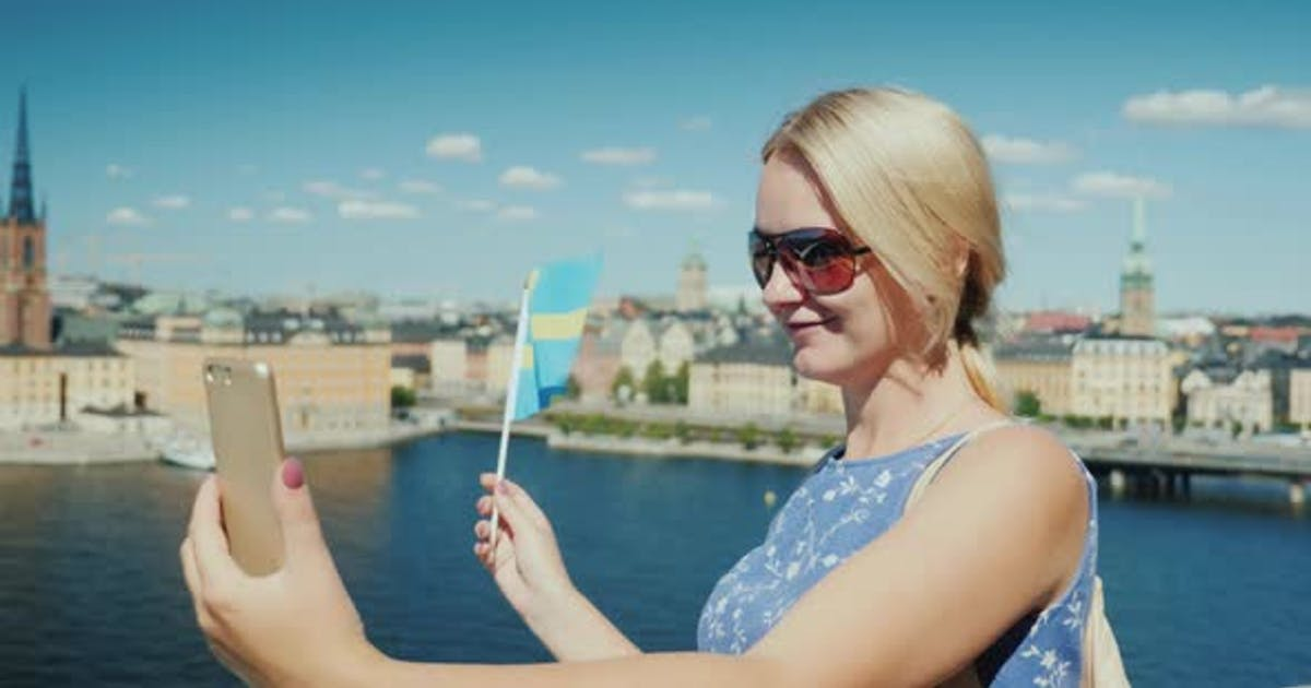 A Happy Tourist with the Flag of Sweden Takes Pictures of Himself Against the Backdrop of Stockholm