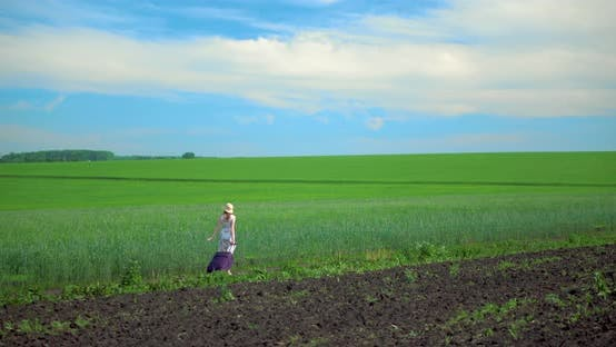 A Girl in a Dress and a Hat Walks Through a Green Field of Grass.